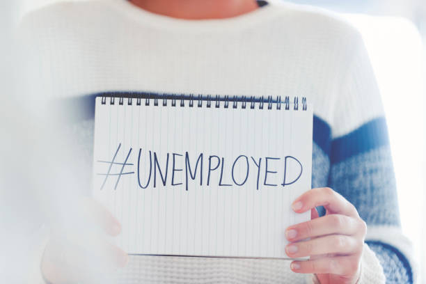 Woman holding a #unemployed sign written on a pad Woman holding a #unemployed sign written on a pad. Human resources, recession or economic depression concept downsizing unemployment stock pictures, royalty-free photos & images