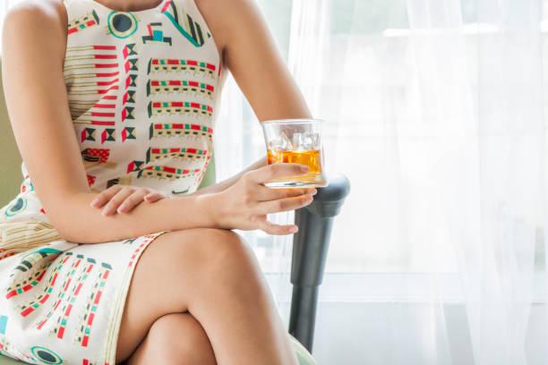 Frau hält einen Whisky an der Bar. Ferienkonzept. – Foto