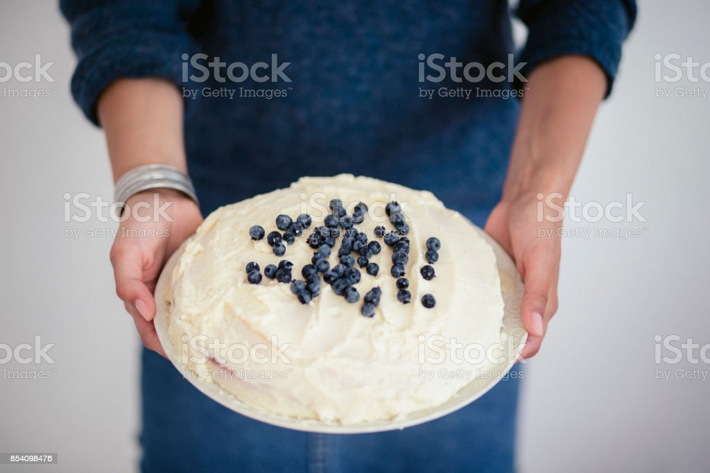Woman holding a white cake with blueberries on top stock photo