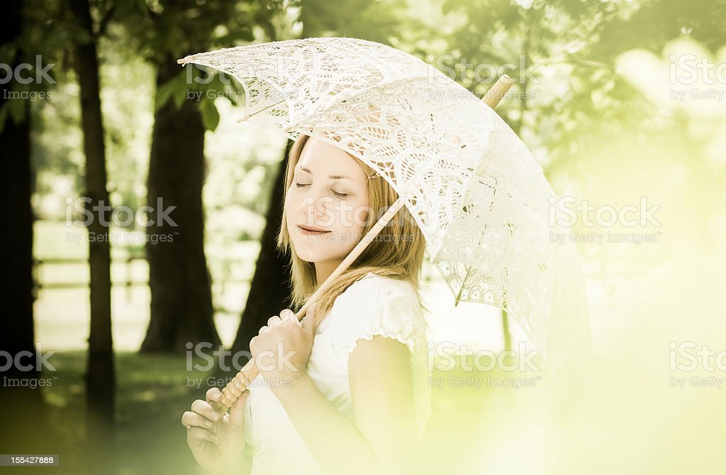 Woman Holding a White Lace Parasol on a Sunny Day royalty-free stock photo