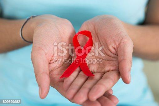 istock Woman Holding Aids Awareness Ribbon 609699582