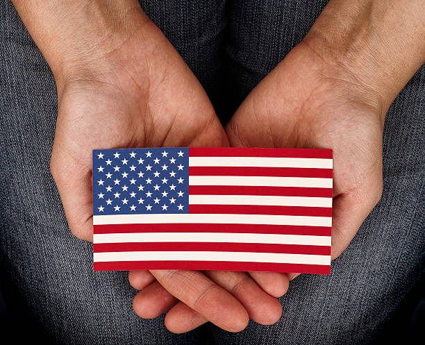 woman holding american flag on her palms - citizenship stock photos and pictures