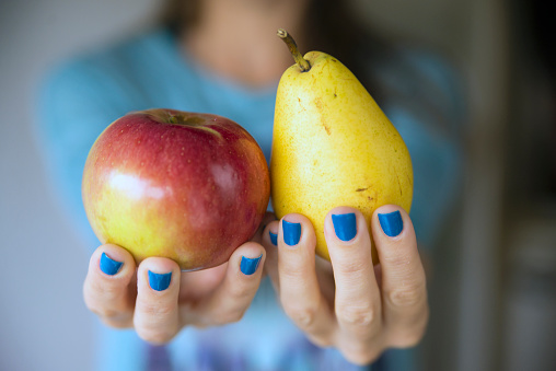 woman holding an apple and a pear