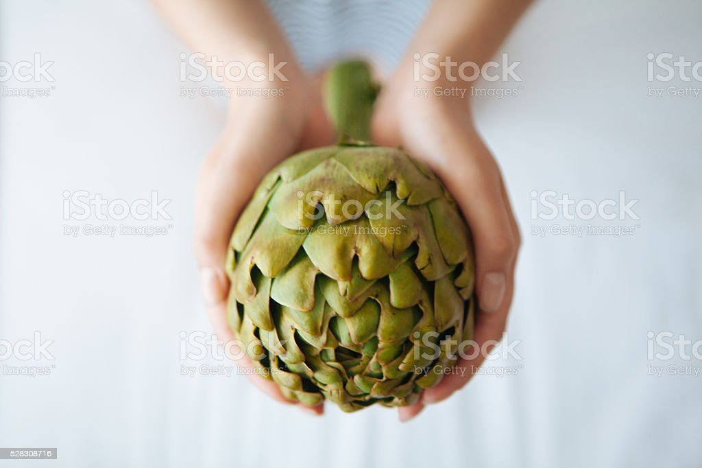 woman holding an artichoke stock photo