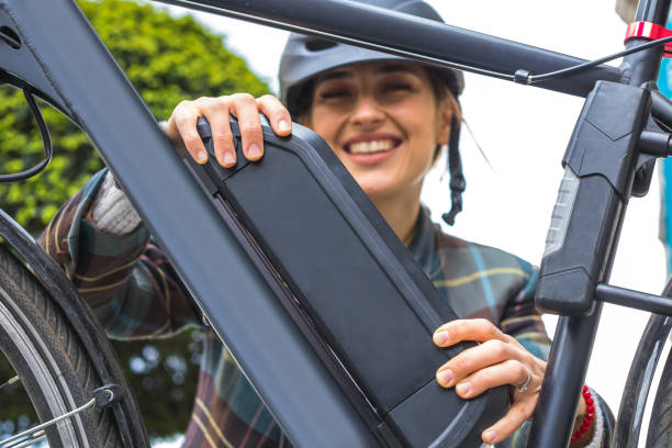 woman holding an electric bike battery mounted on frame stock photo