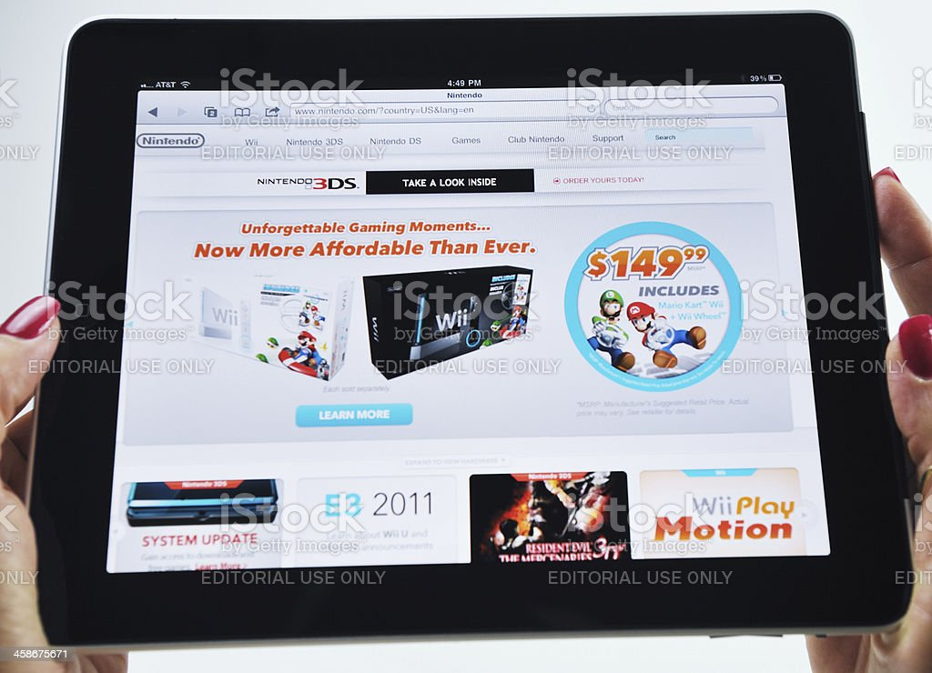Woman Holding an iPad Displaying a Nintendo Video Game royalty-free stock photo