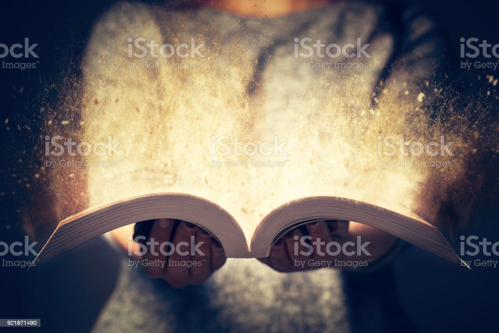 Woman holding an open book bursting with light. stock photo