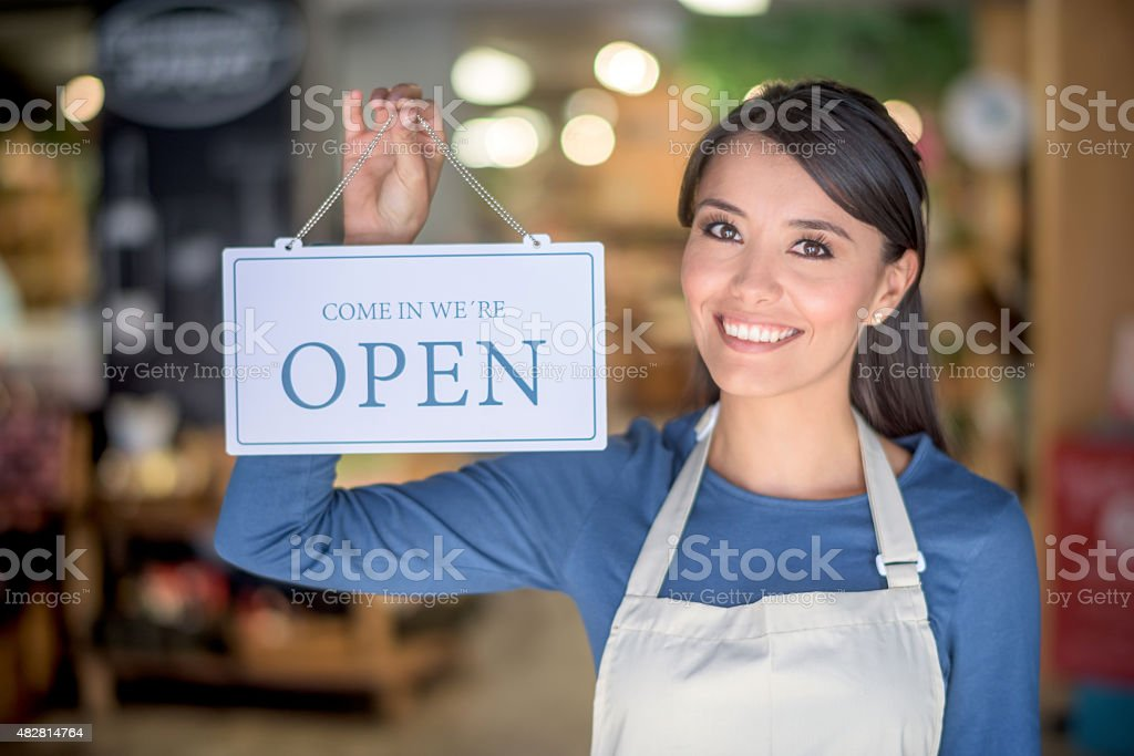 Woman Holding An Open Sign At A Grocery Store Stock Photo