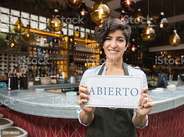 Woman holding an open sign in spanish at a restaurant picture id525498404?b=1&k=6&m=525498404&s=612x612&h=ubkllqgtq9asegvqwr4kn24t qawrxiv4q1dqkbdwq4=