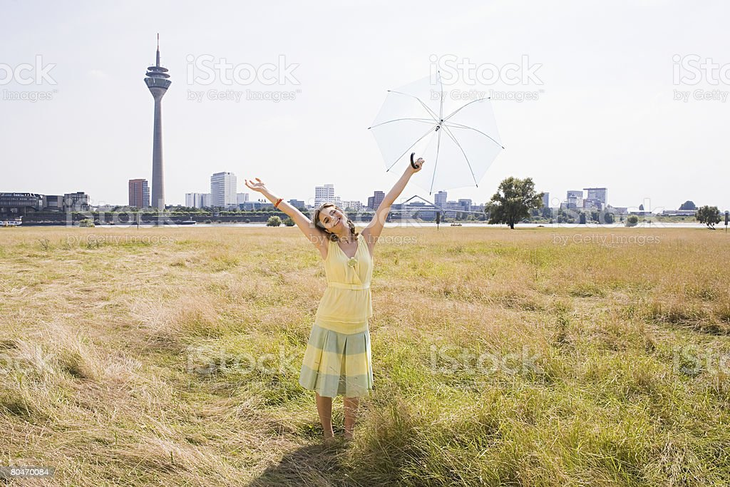 Woman holding an umbrella in a field 免版稅 stock photo