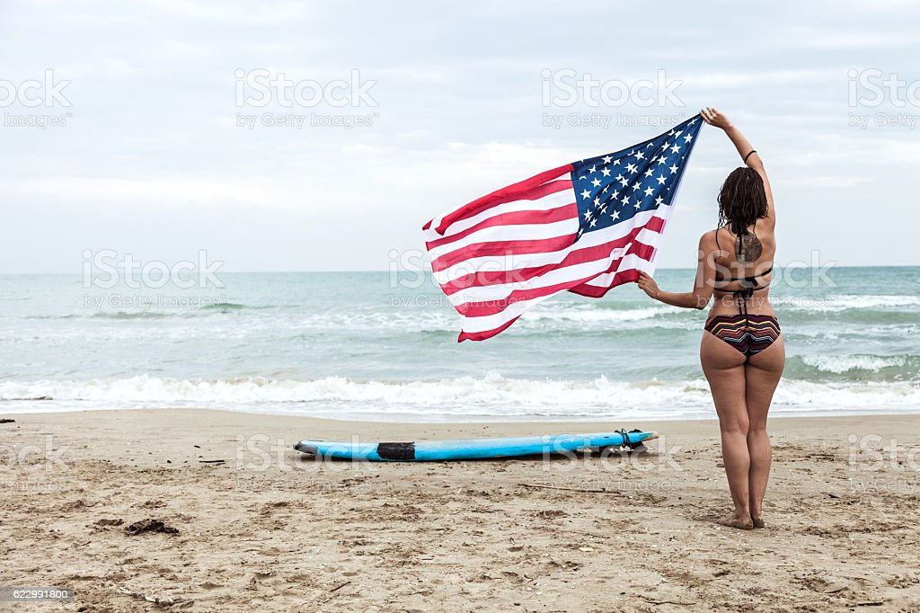 Woman holding an US flag before starting the surf day - foto de stock