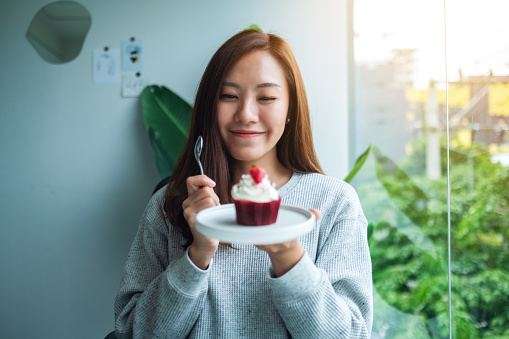 A beautiful asian woman holding and eating a red velvet cupcake