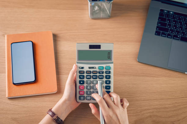 Woman holding and press calculator to calculate income expenses and plans for spending money on home office. stock photo