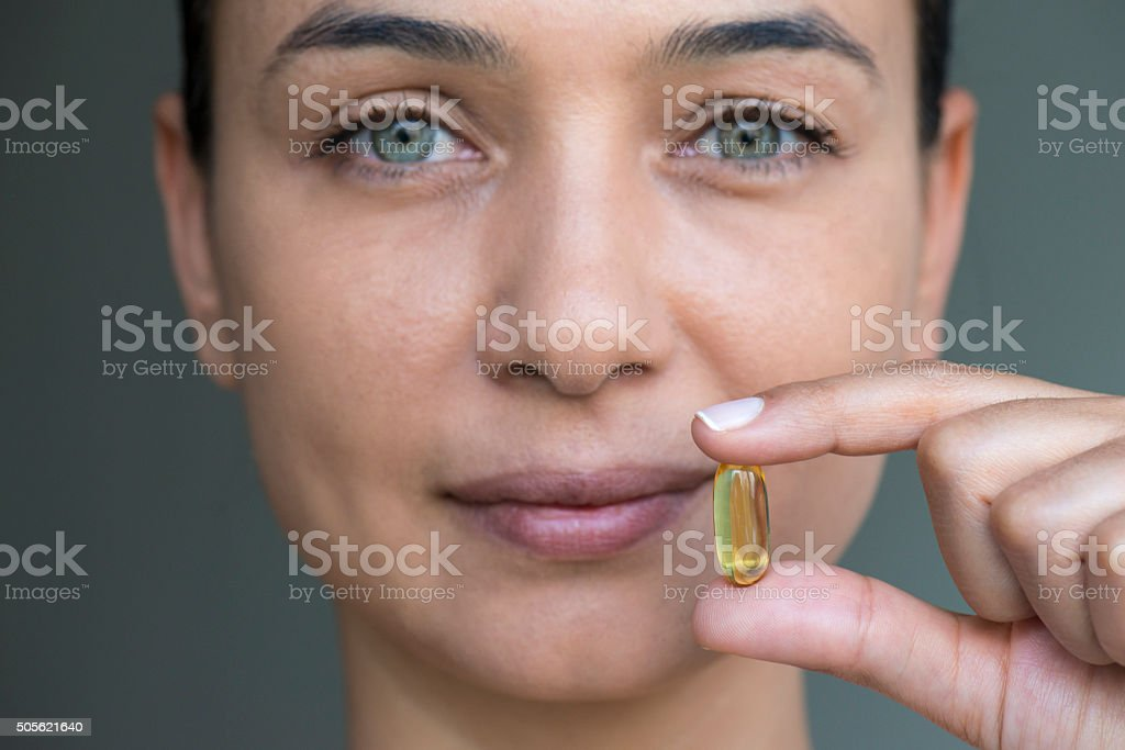 Woman Holding And Showing Soft Gel Capsule stock photo
