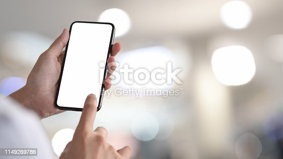 Woman holding and touching blank screen smartphone in bokeh background