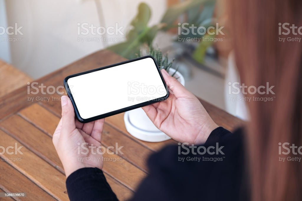 Mockup image of woman holding and using a black mobile phone with...