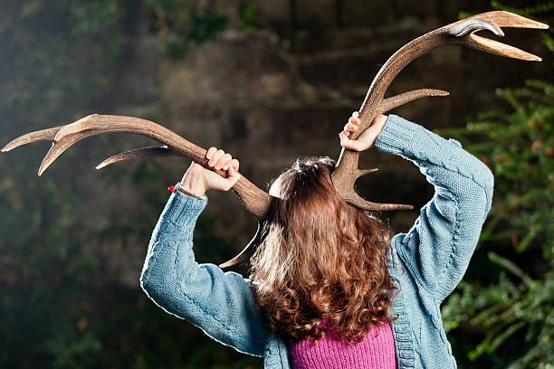 frau holding antlers auf dem kopf - deko geweih stock-fotos und bilder