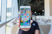 istock Woman holding Apple iPhone 6S Rose Gold with icons of social media on screen. Social media are most popular tool.  Smartphone life style. Starting social media app. 1162303314
