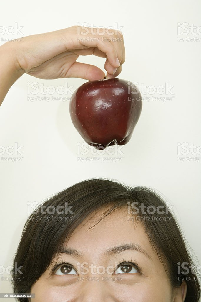 Woman holding apple over head, high section foto royalty-free