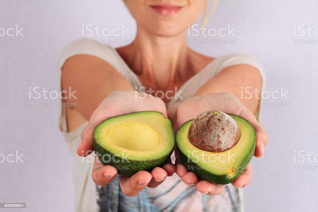 Woman holding avocado closeup. stock photo