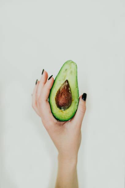 Woman holding avocado on white background stock photo