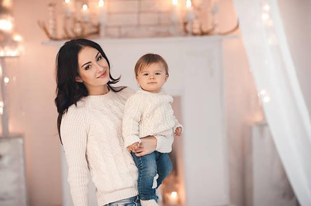 woman holding baby girl over christmas lights - festliche babymode junge stock-fotos und bilder