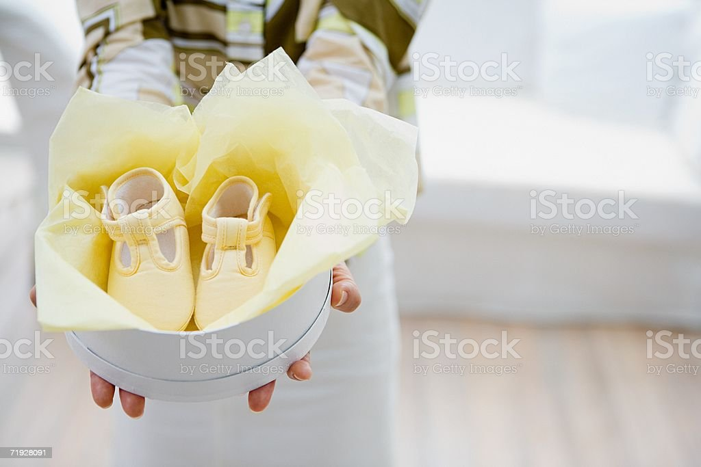 Woman holding baby shoes in a box royalty-free stock photo