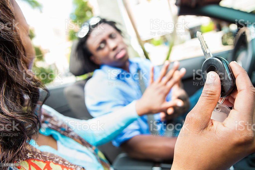 Woman holding back car key from driver stock photo