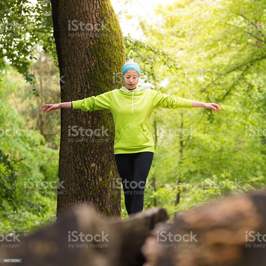 Frau hält Gleichgewicht auf Baumstamm im Natur. Lizenzfreies stock-foto