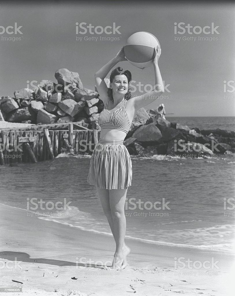 Woman holding ball on beach, (B&W) stock photo