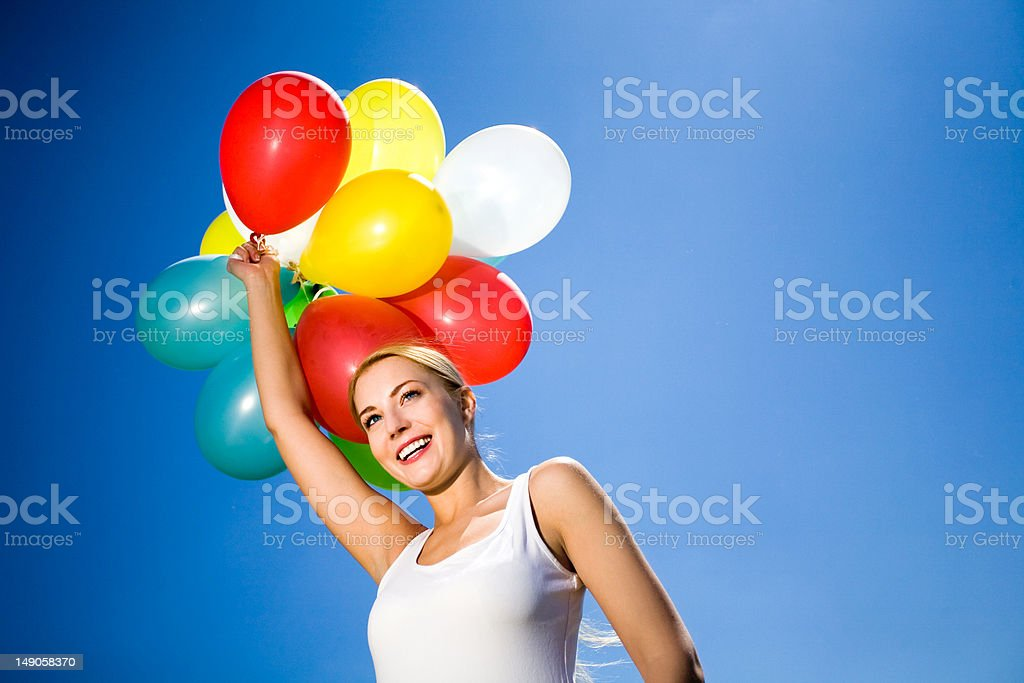 Woman holding balloons against blue sky royalty-free stock photo
