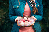 Woman holding basket with Easter eggs in nature