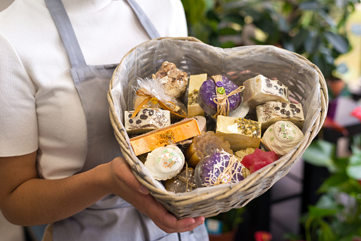 Woman entrepreneur holding basket with home made soaps.