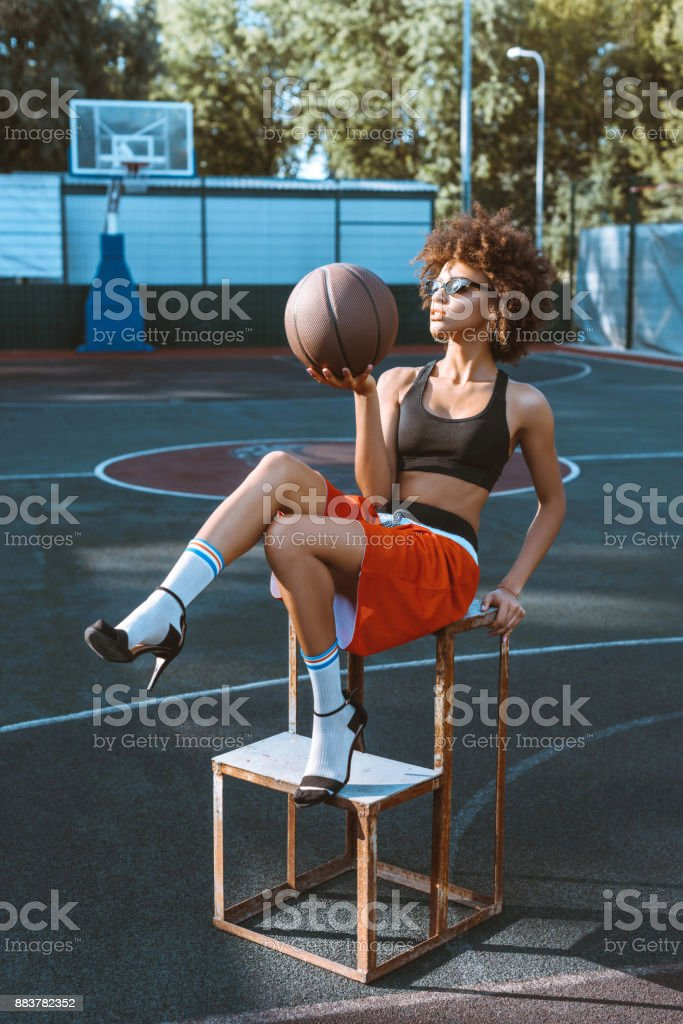 Young african-american woman in sportive attire and high heels...