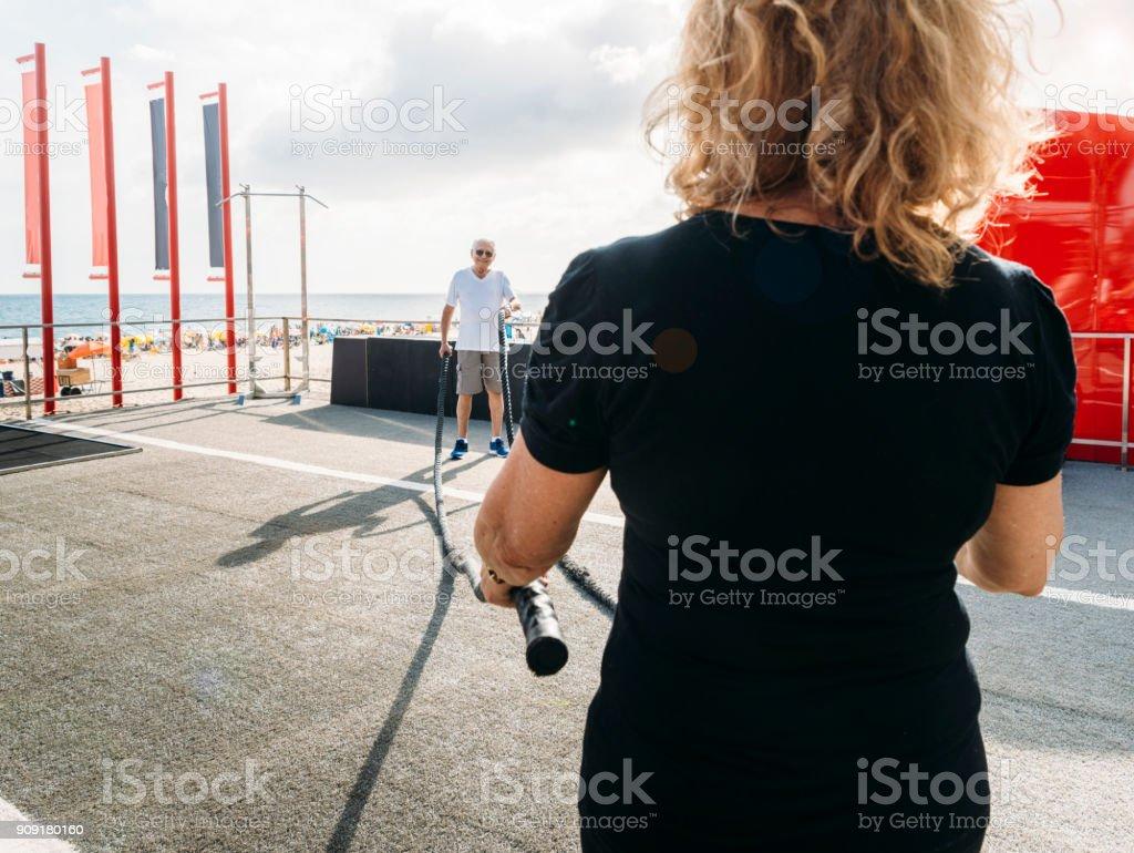 Frau mit kämpfenden Seil mit älteren Mann im Hintergrund, in Ipanema, Rio De Janeiro, Brasilien – Foto