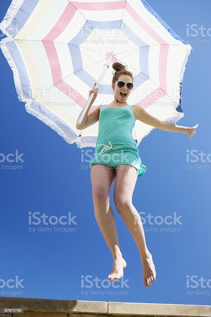 Woman holding beach umbrella and jumping off ledge royalty-free stock photo