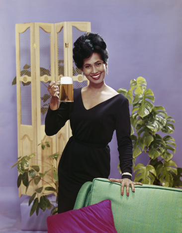 Woman holding beer glass beside sofa, smiling, portrait