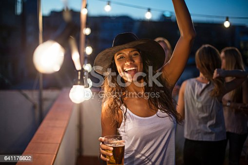 Portrait of cheerful woman dancing during party. Happy female is holding beer glass while enjoying on illuminated terrace. Friends are celebrating during dusk.