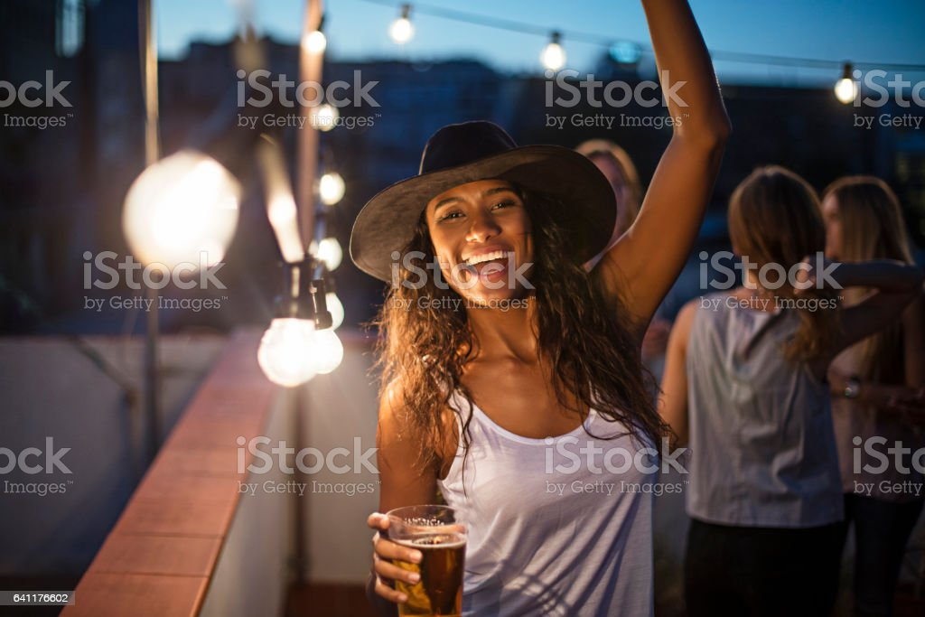 Woman holding beer glass while dancing on terrace stock photo