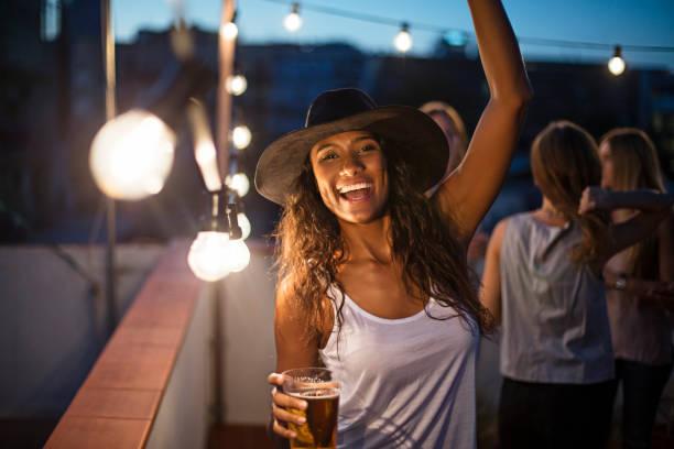 Femme tenant le verre de bière tout en dansant sur la terrasse - Photo