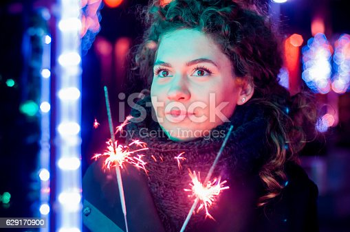 istock Woman holding bengal lights over bokeh background. Christmas concept 629170900