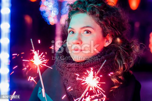 istock Woman holding bengal lights over bokeh background. Christmas concept 629170974