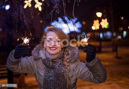 istock Woman holding bengal lights over bokeh background. Christmas concept 641629332