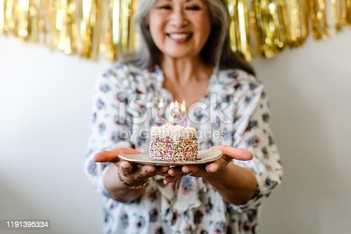 Smiling senior woman holding birthday cake with burning candles. Retired female is standing with dessert against wall. She is celebrating at home.