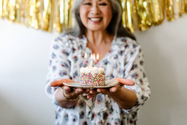 Woman holding birthday cake with burning candles Smiling senior woman holding birthday cake with burning candles. Retired female is standing with dessert against wall. She is celebrating at home. 65 69 years stock pictures, royalty-free photos & images