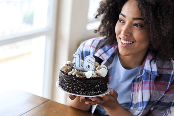Woman holding birthday cake with candles 16 stock photo