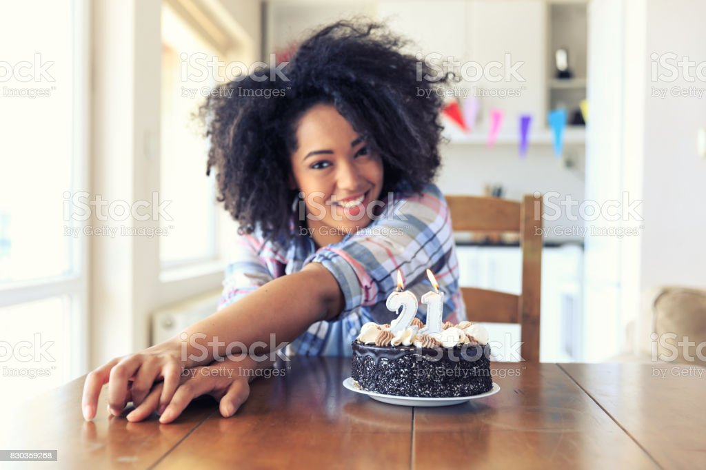 Woman holding birthday cake with candles 21 stock photo