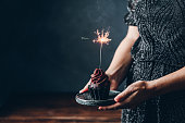 istock Woman holding birthday cupcake with firework candle 1266799449