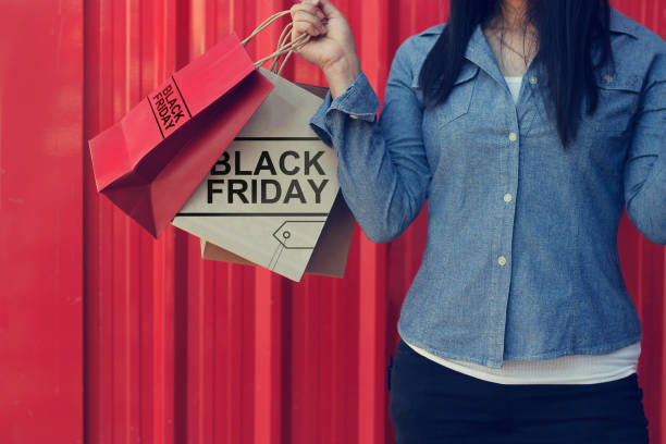 Woman holding Black Friday shopping bag while standing on red metal wall of shopping mall background stock photo