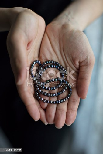 Woman Holding Black Pearl Necklace